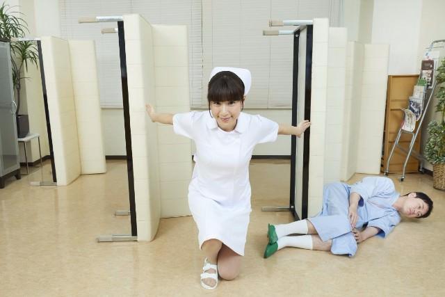 病室の長椅子を縦にしてポーズをとる看護師